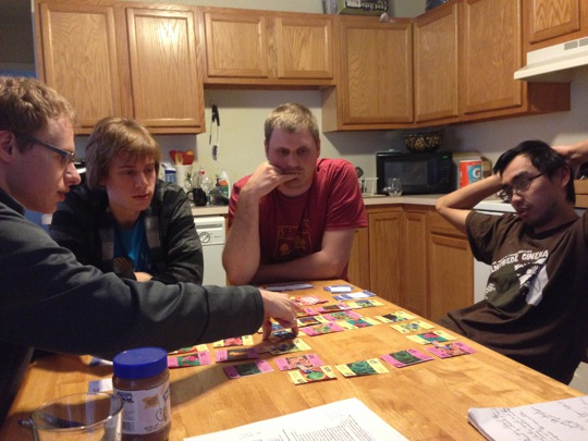 4 players around a table playing the educational card game Conjugation.