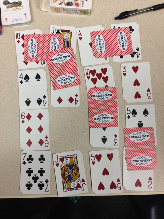 Playing cards on a table arranged in a 4 by 4 grid. Some cards are face down and bridging other cards.