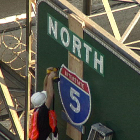 Artist disguised as a government construction worker alters a highway sign.