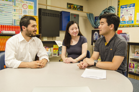 A teacher, parent, and translator having an in-person meeting in a classroom.
